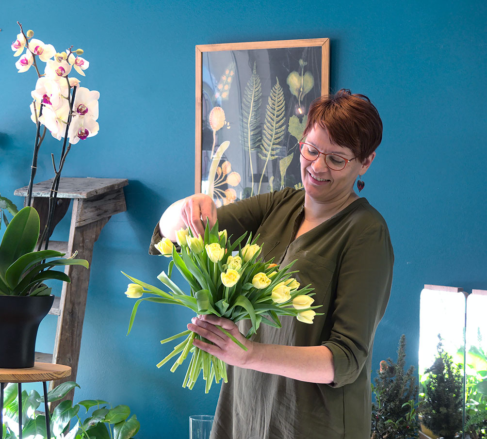 Nainen asettelee kukkia