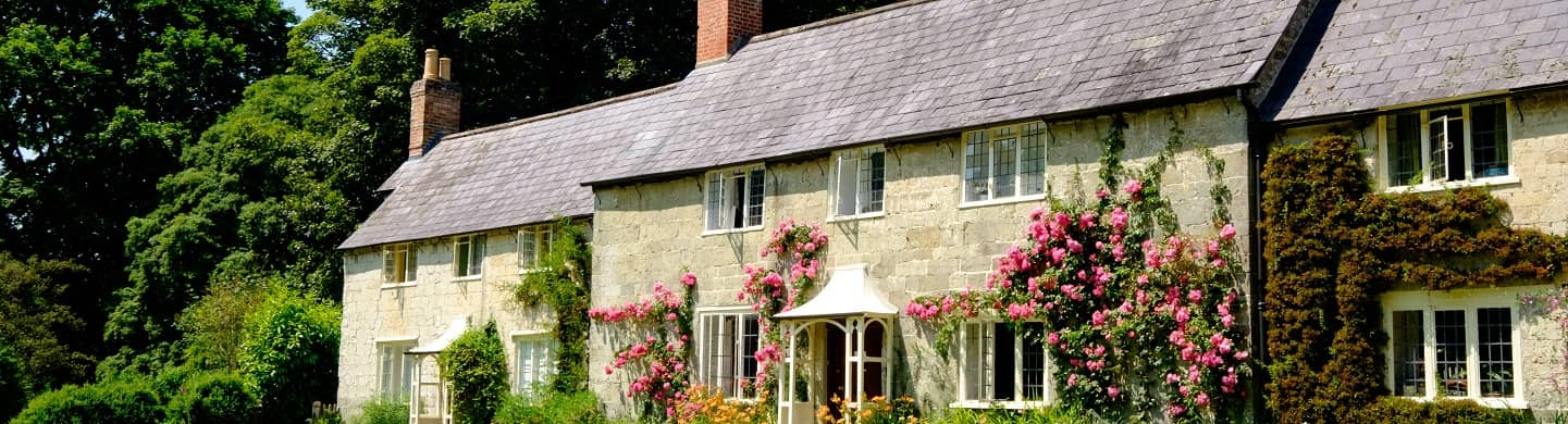 Cottages set behind luscious green grass with roses climbing the front of the building