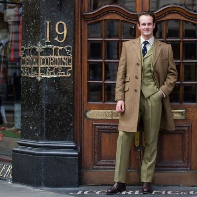 A man in a tweed suit stood outside of the shop front for Cordlings