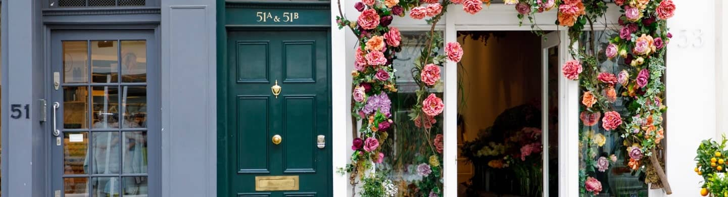 A blue shop front, a green door and a doorway lined with pink flowers