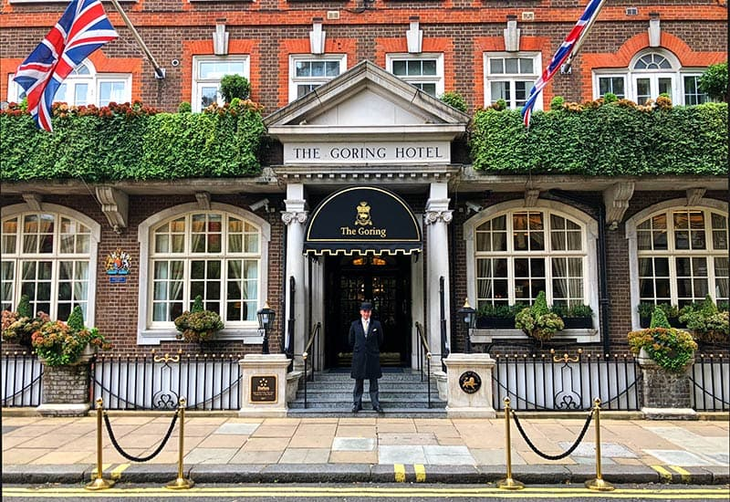 The front of the Goring hotel featuring white pillars and window boxes full of shrubbery