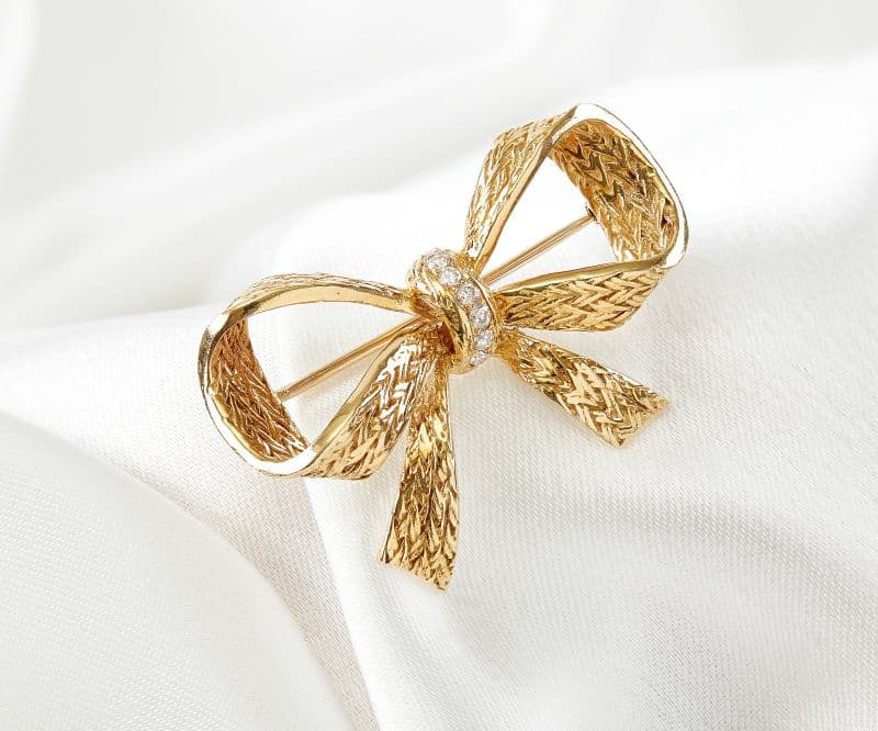 A gold bow pin with a diamonds placed in the center