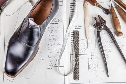 A shoe and shoe makers tools placed on a piece of paper with writing on