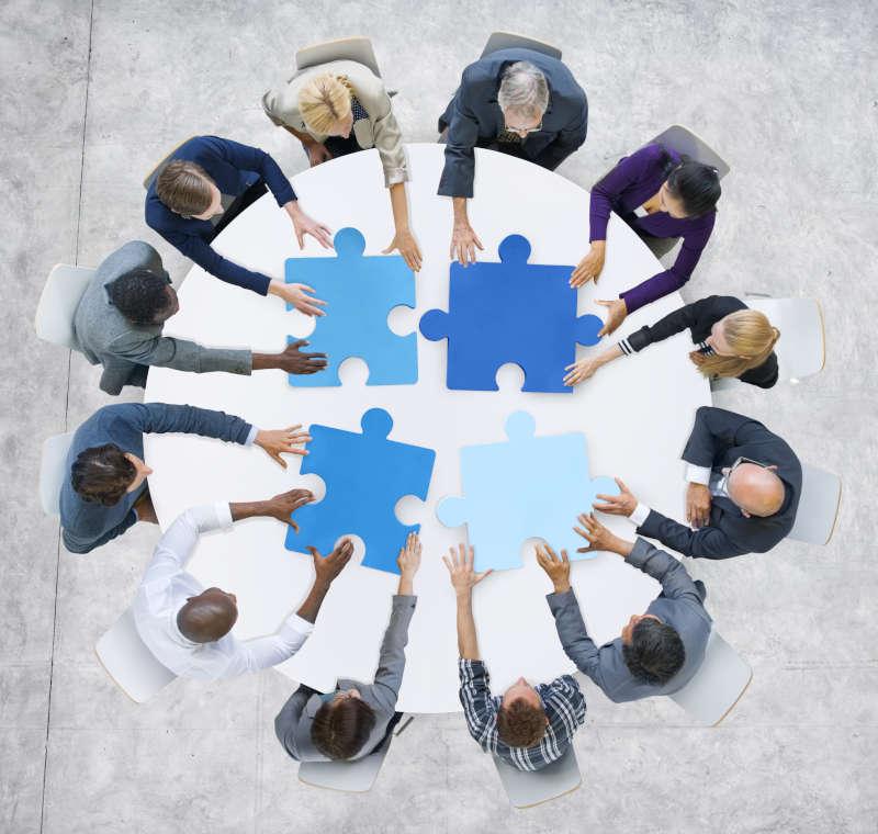 Cirkel van mensen met vier passende puzzultukjes