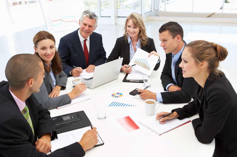 Zakelijke collega's die samenwerken aan een vergadertafel.
