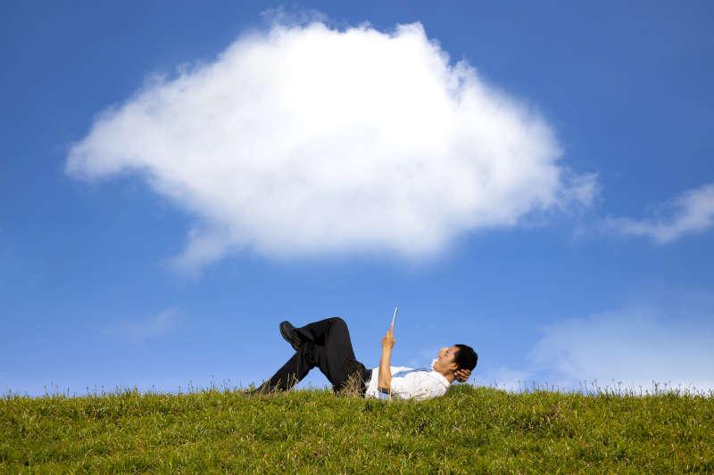 Persoon die met een telefoon in de hand op de gras ligt.