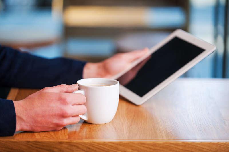 Kopje koffie drinken met een tablet in de hand