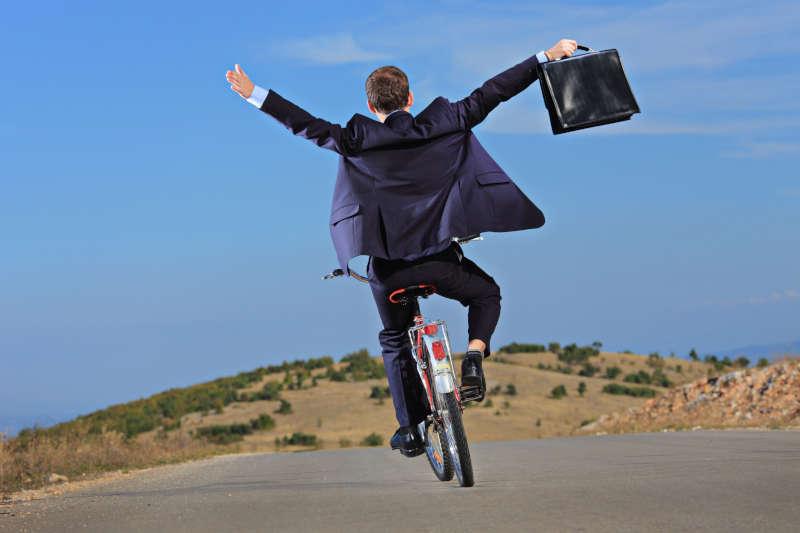 Man met een koffer op een fiets.