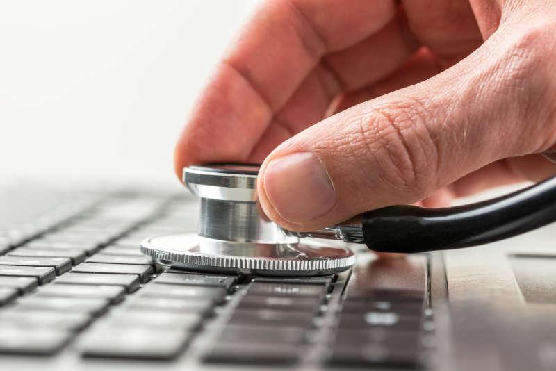 Hand die een stethoscoop vasthoud boven een toetsenbord.