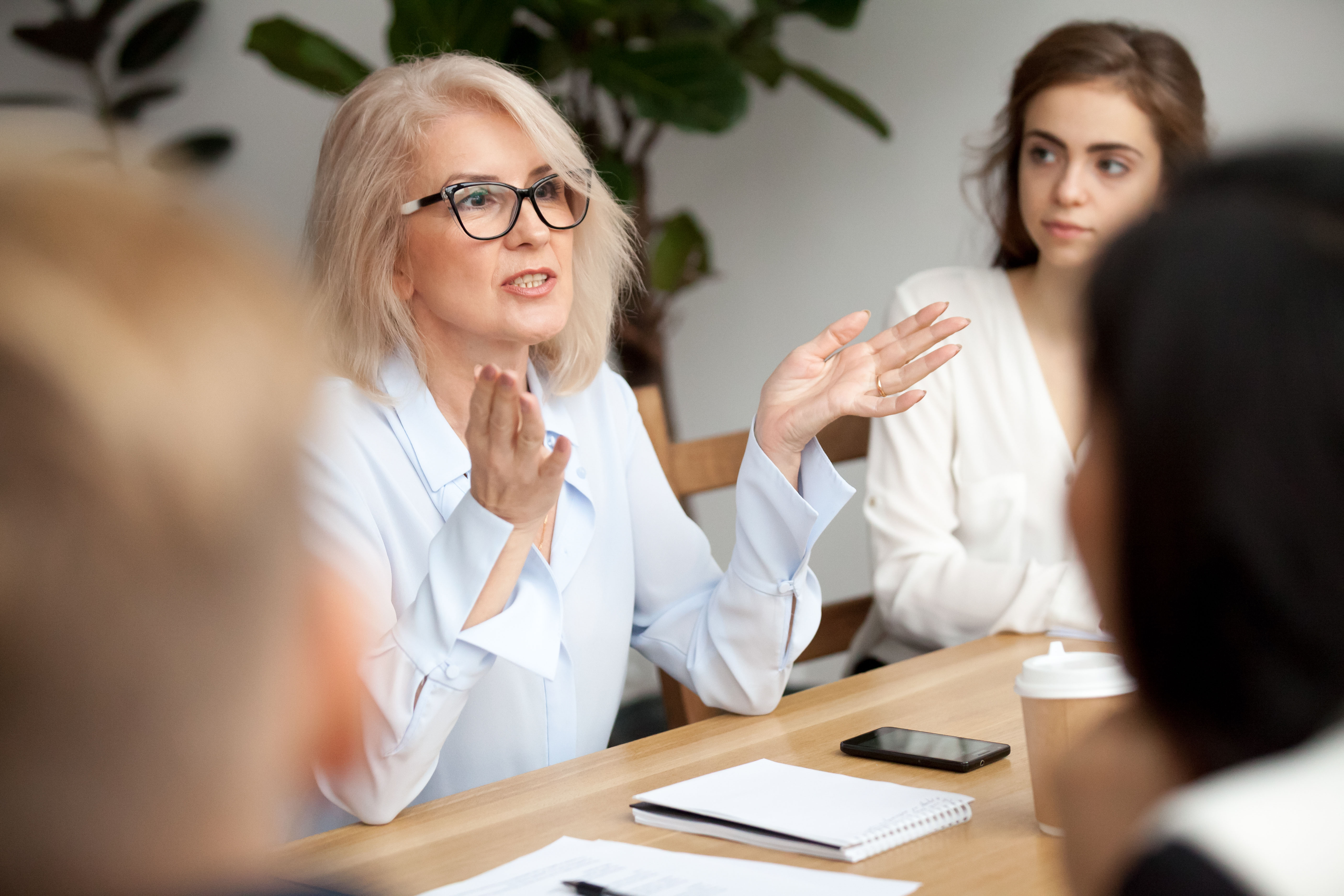 woman with glasses explaining something in a meeting