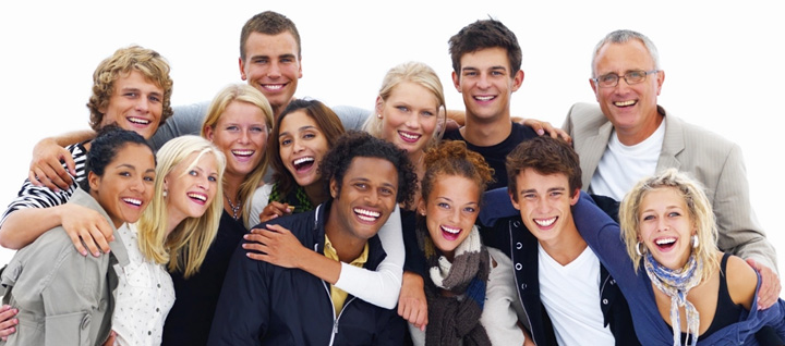 diverse group of people smiling in a group facing the camera with their hands on each others shoulders