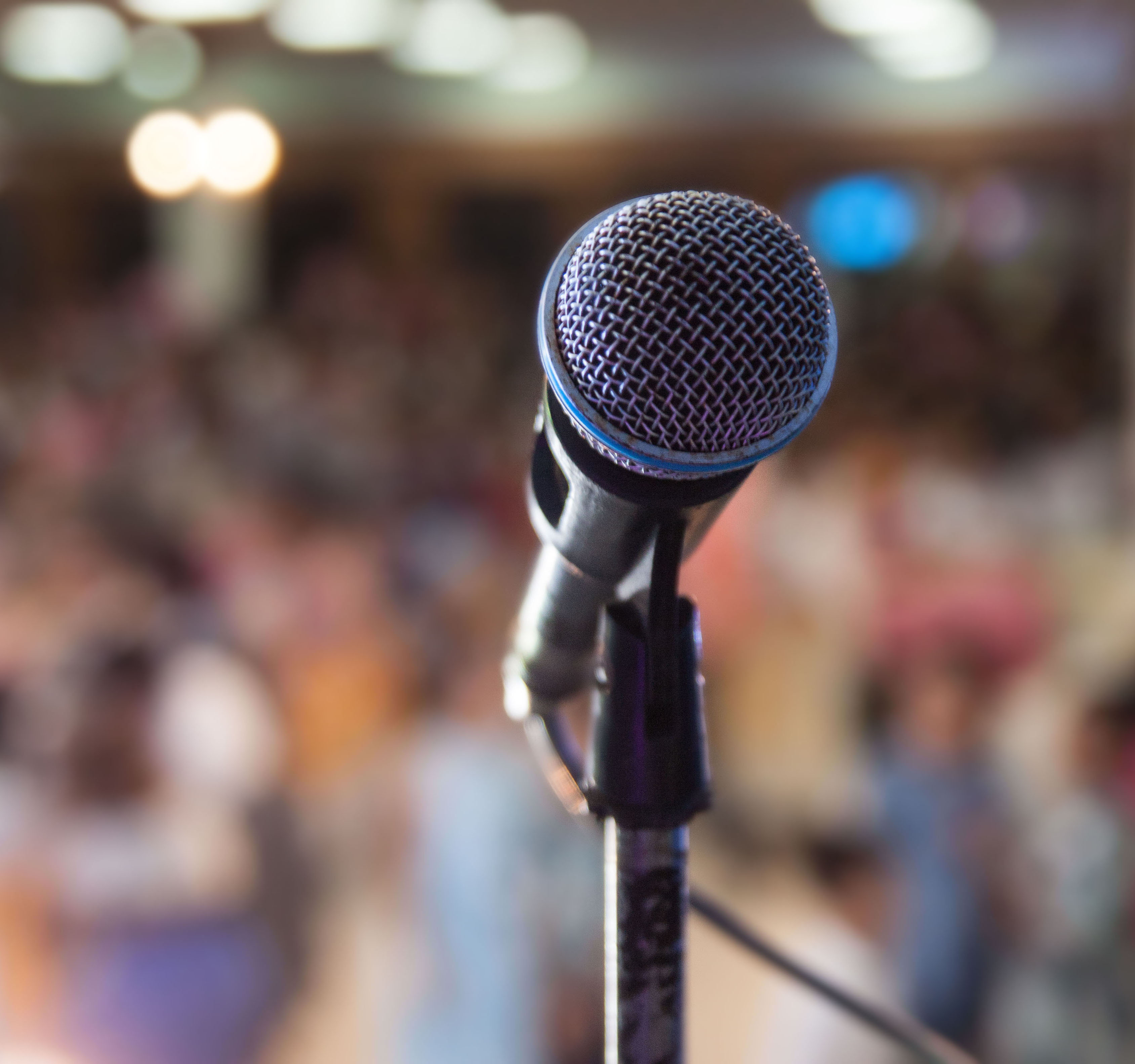 solo microphone in front of a blurred out crowd