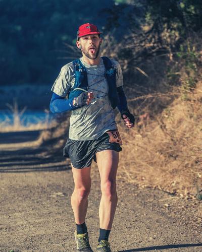 A trail runner heading down a dirt trail
