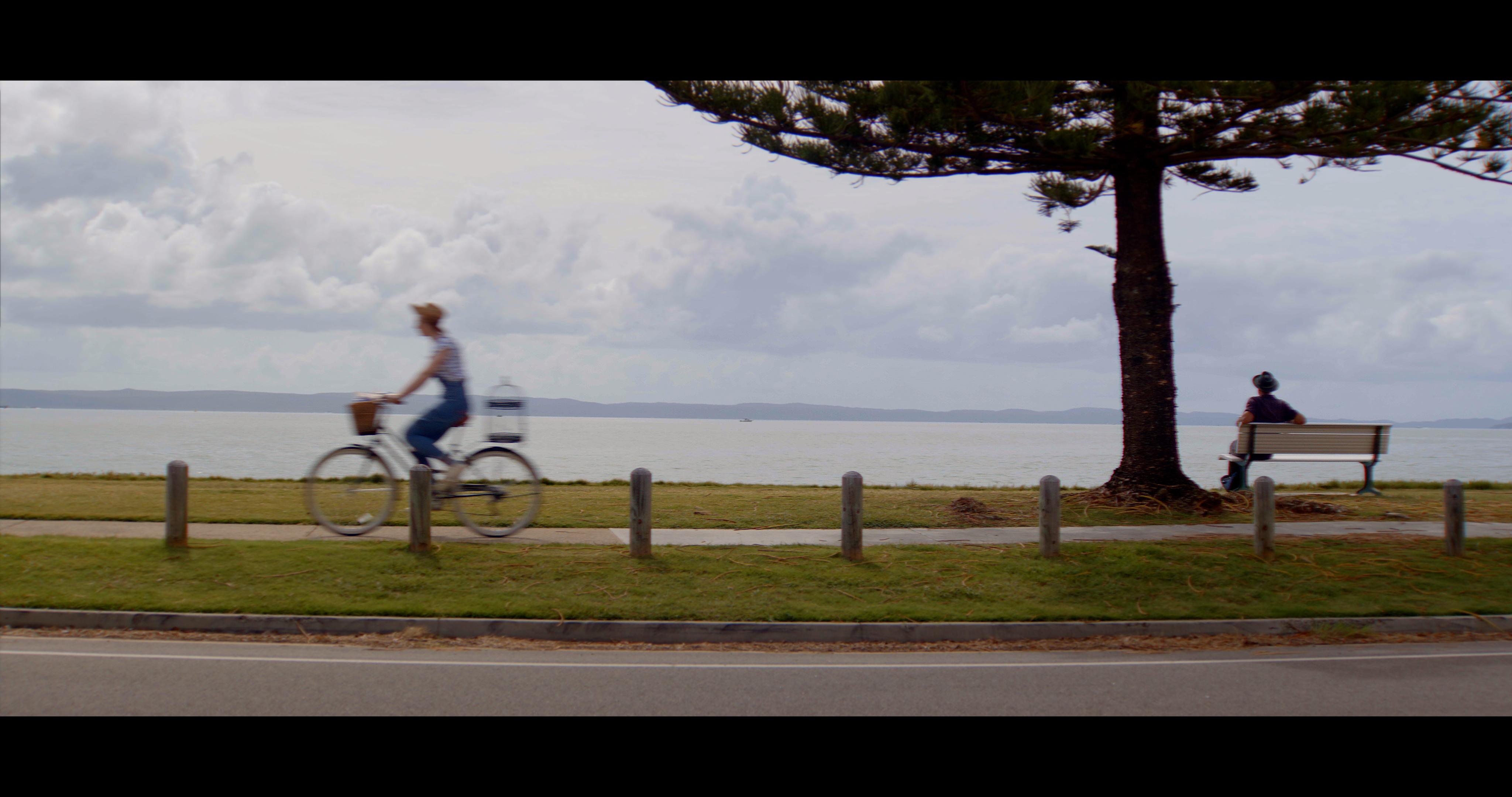 Caroline riding bike past sea side vista. Caged Creatures.