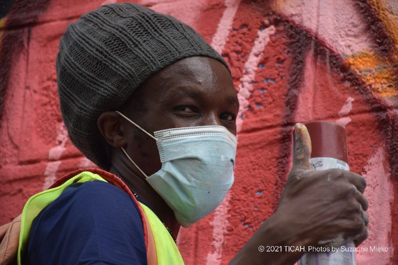 Artist giving a thumbs-up while painting a mural at Muthurwa roundabout