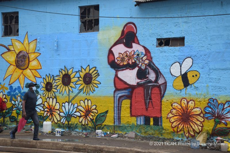 Painting of a seated woman working at the mural at Muthurwa roundabout