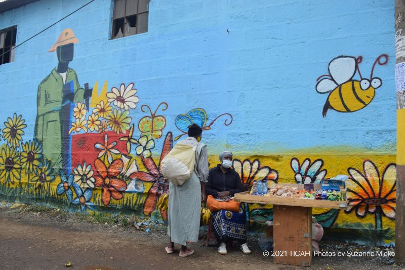 Two working women chatting in-front of the mural at Muthurwa roundabout