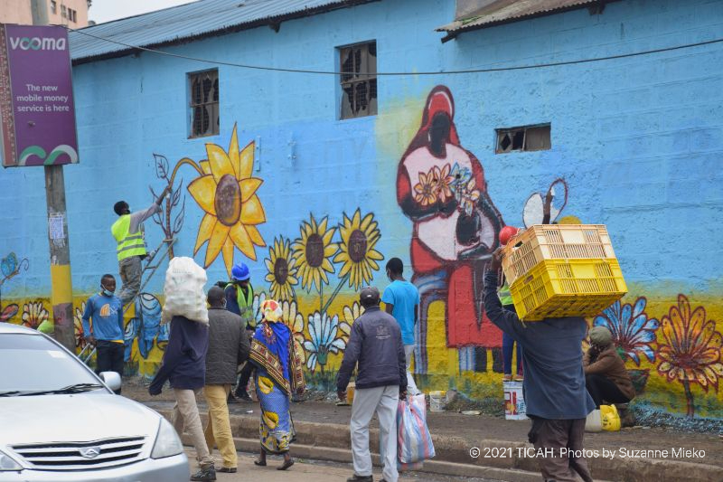 People in the streets passing by the mural at Muthurwa roundabout