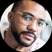 Retrato de um homem negro de barba, sério, olhando para a câmera