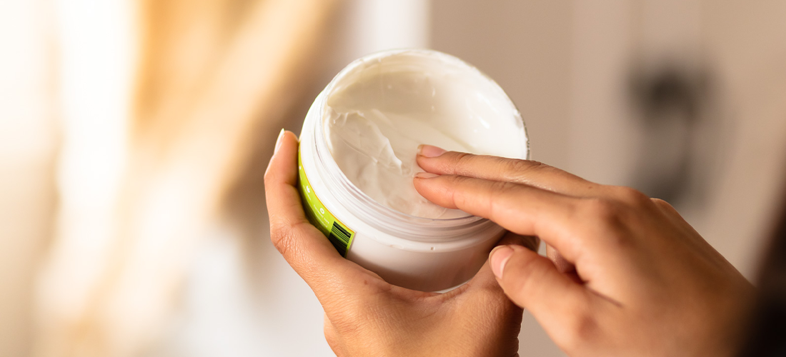 Two fingers touching lotion in a cylinder container