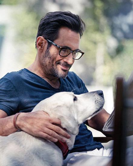 Gregory Zarian reading newspaper while petting a white Labrador retriever