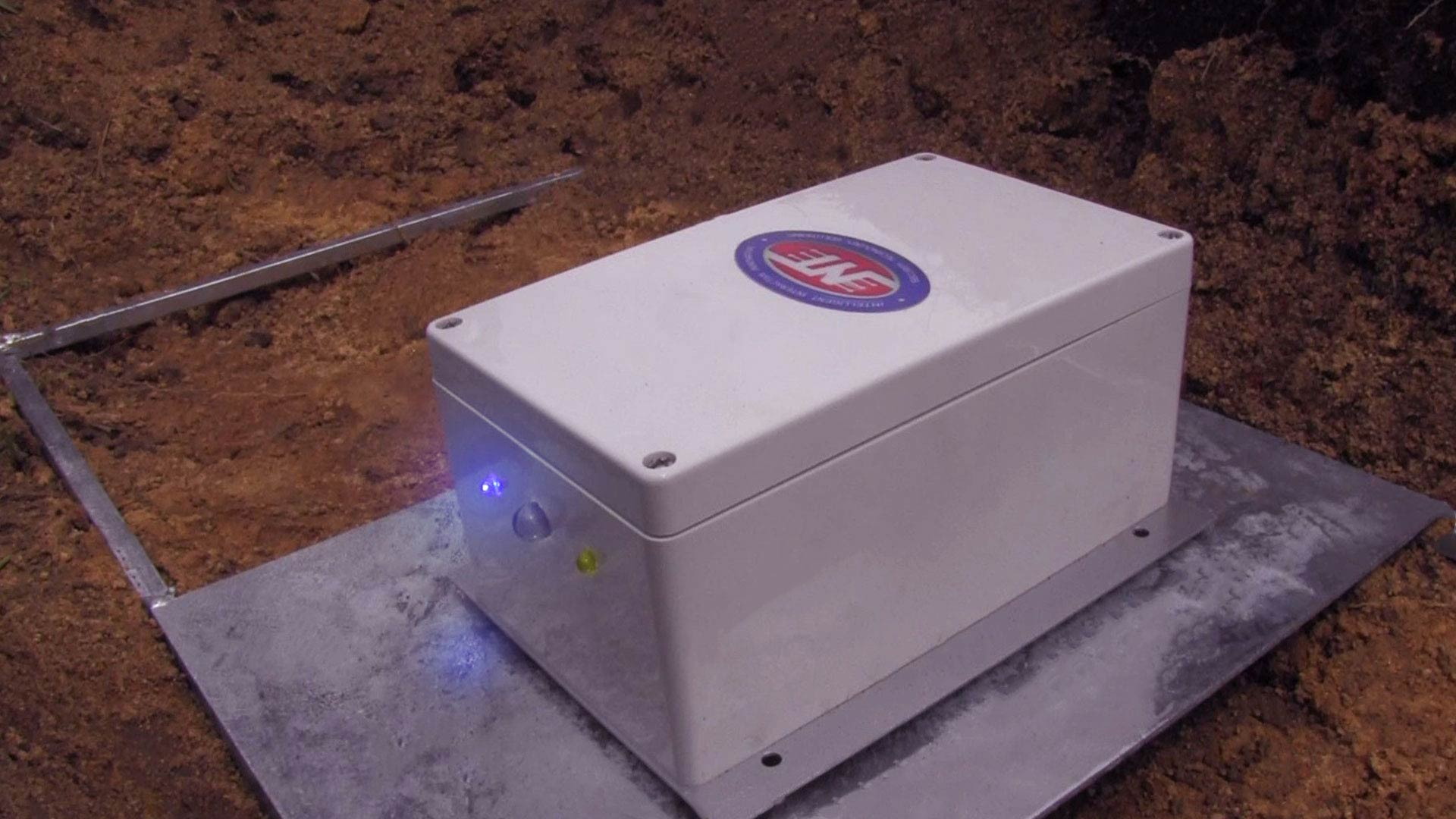 Underground alarm being tested in the field before installation. This device is placed on a metal frame that is designed to increase the vibration detection radius.