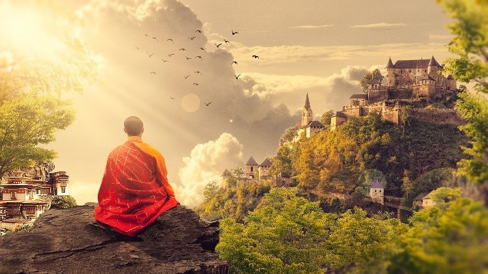 monk meditating on the mountain in front of castle
