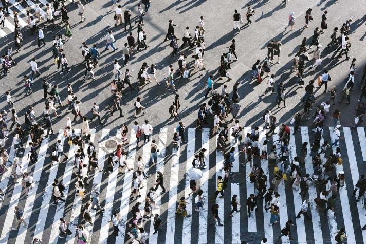 a lot of people walking on pedestrian crossings