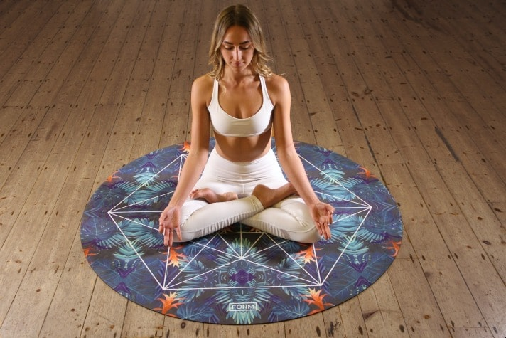 woman in the lotus position on a yoga mat while meditating