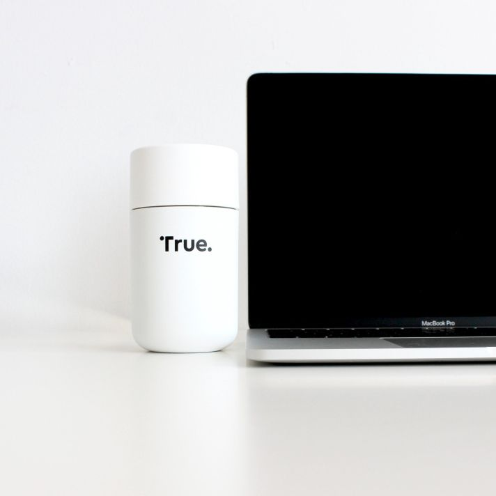 white box with true written on the front next to a macbook pro