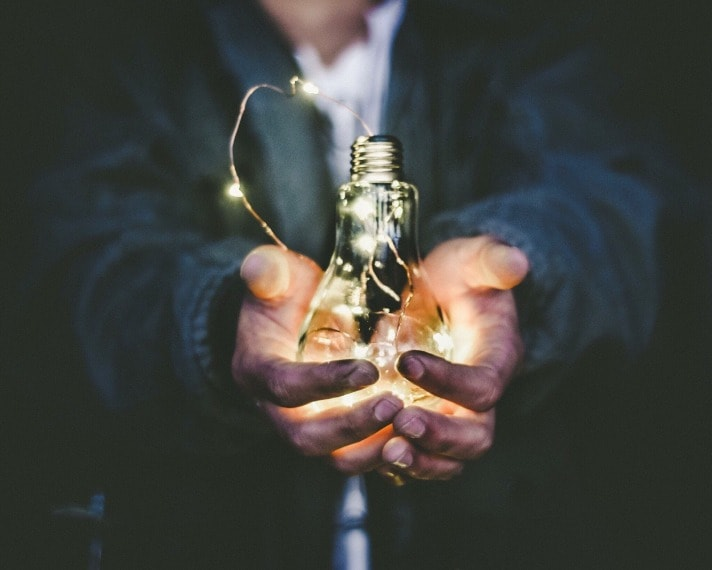 lighted bulb in a person hands