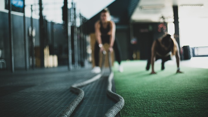 two girls training in a crossfit gym, one doing push-ups while the other holds conditioning ropes