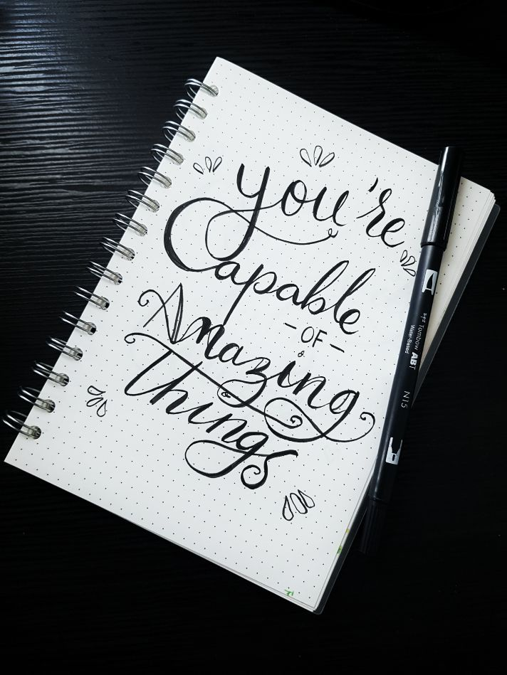 open notepad with writing you are capable of amazing things