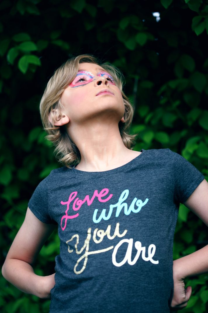 a child proudly wearing a t-shirt with the words love who you are