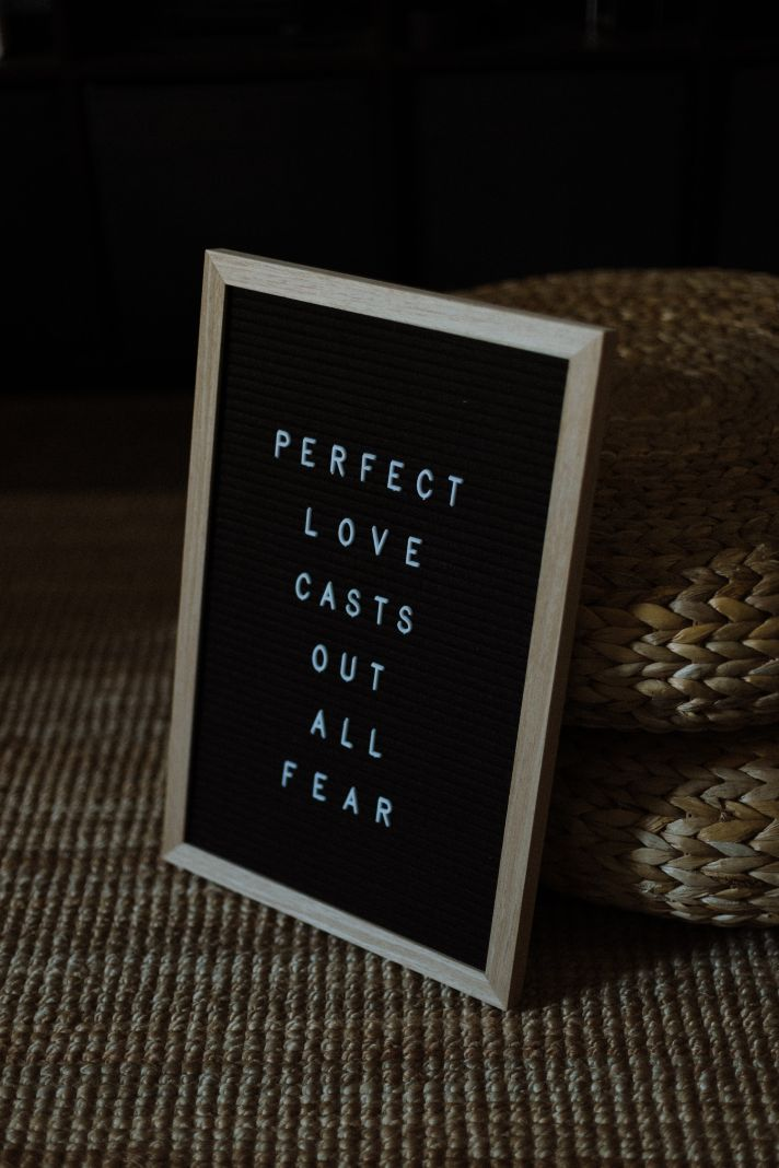 board on black background with white writing perfect love casts out all fear