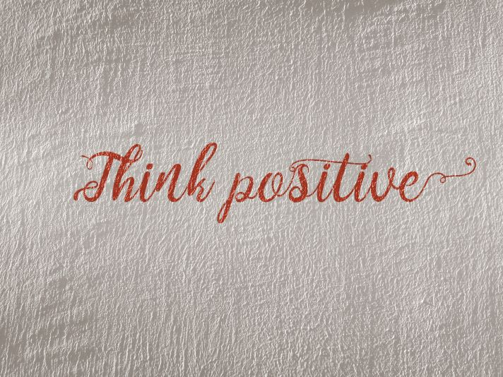 think positive written in red on a white plastered wall
