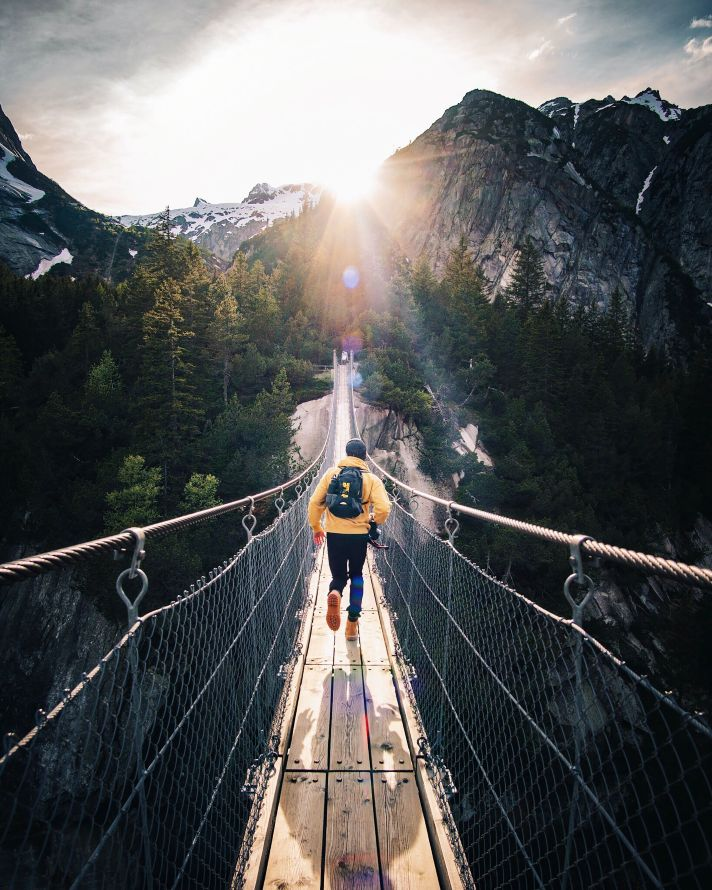 man running on a wooden footbridge in front of the sunrise with mountains and a forest of fir trees