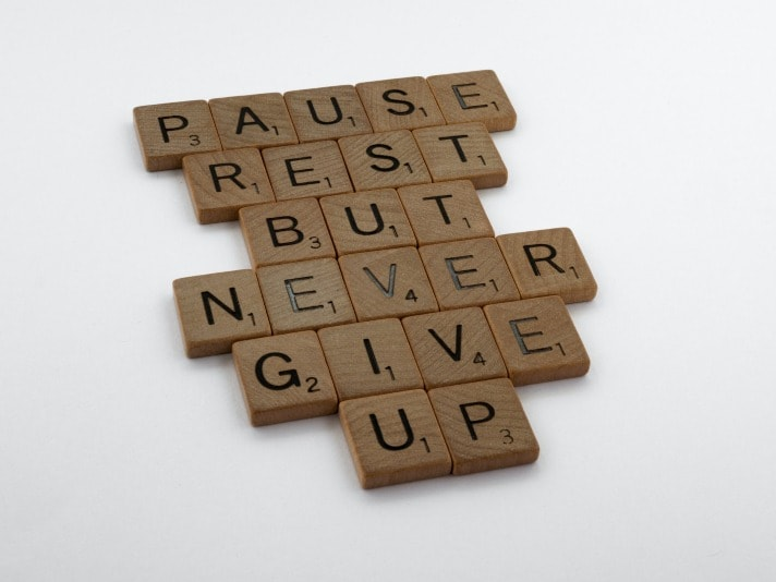 """wooden scrabble letter on a white background """"pause rest but never give up"""""""