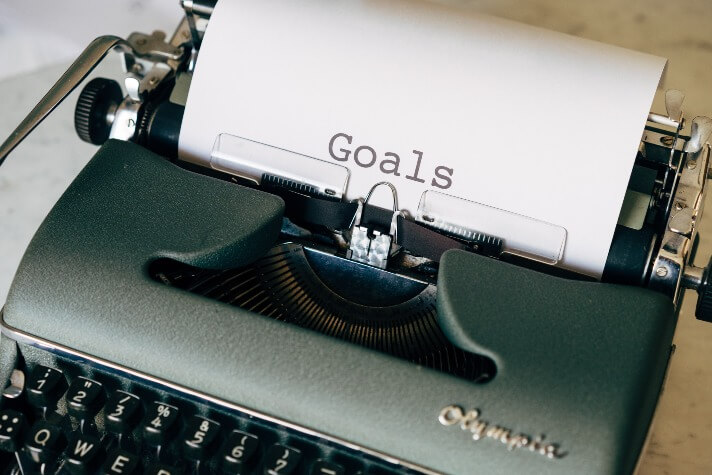 black and white typewriter with goals written on paper