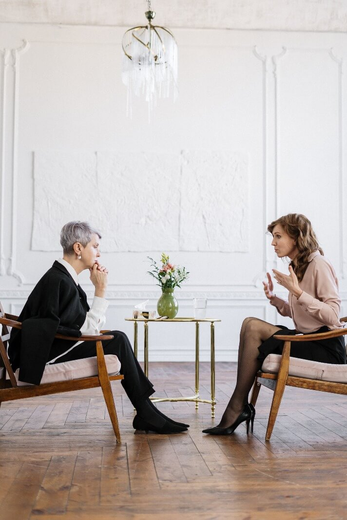 two-women-sitting-on-chairs-and-talking