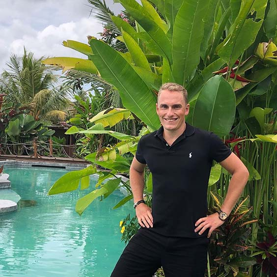 maxime froget in front of a pool and tropical plants