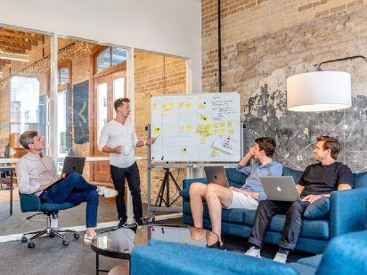 four people in a meeting with one person standing and explaining something in front of a board
