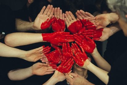 group of people pointing their red painted hands to the sky and forming a heart