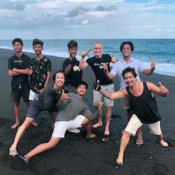 maxime froget with indonesian guys group on a black sand beach