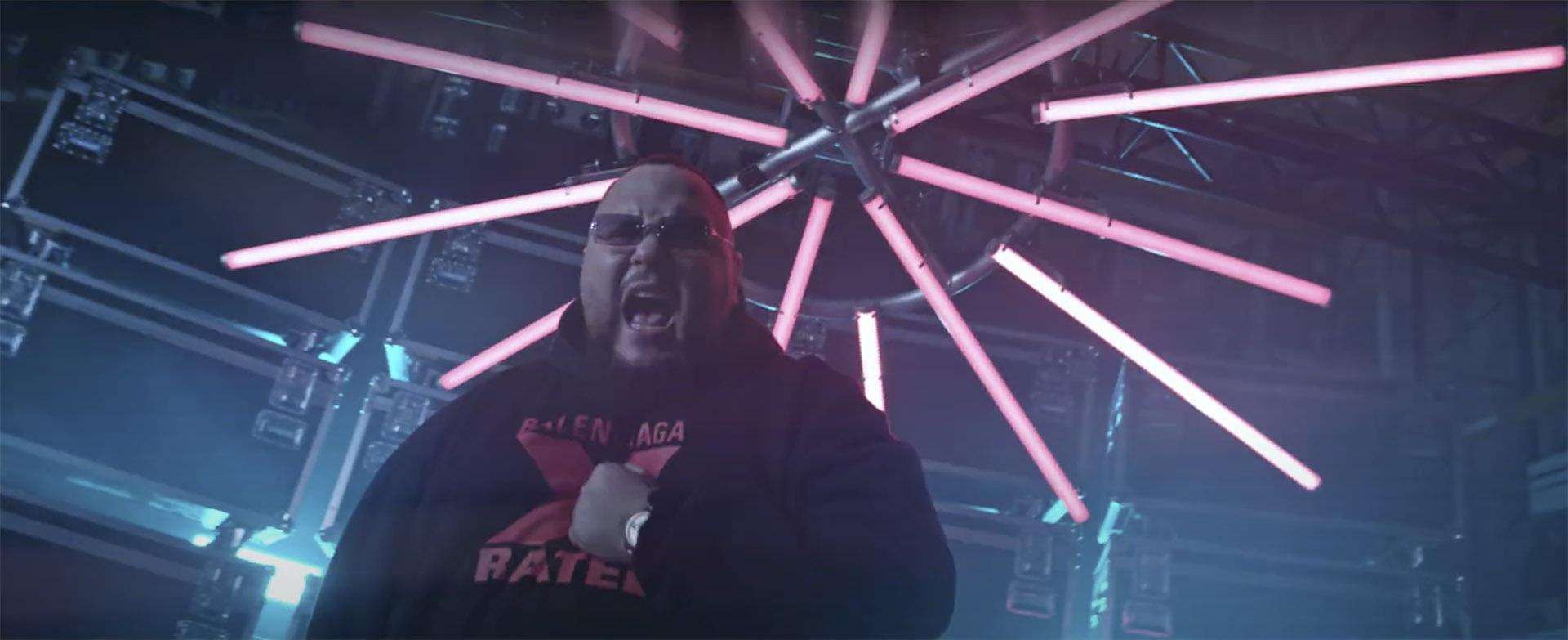 Foto von Rapper Bozza vor einem leuchtenden roten Stern aus roten Titan Tubes.