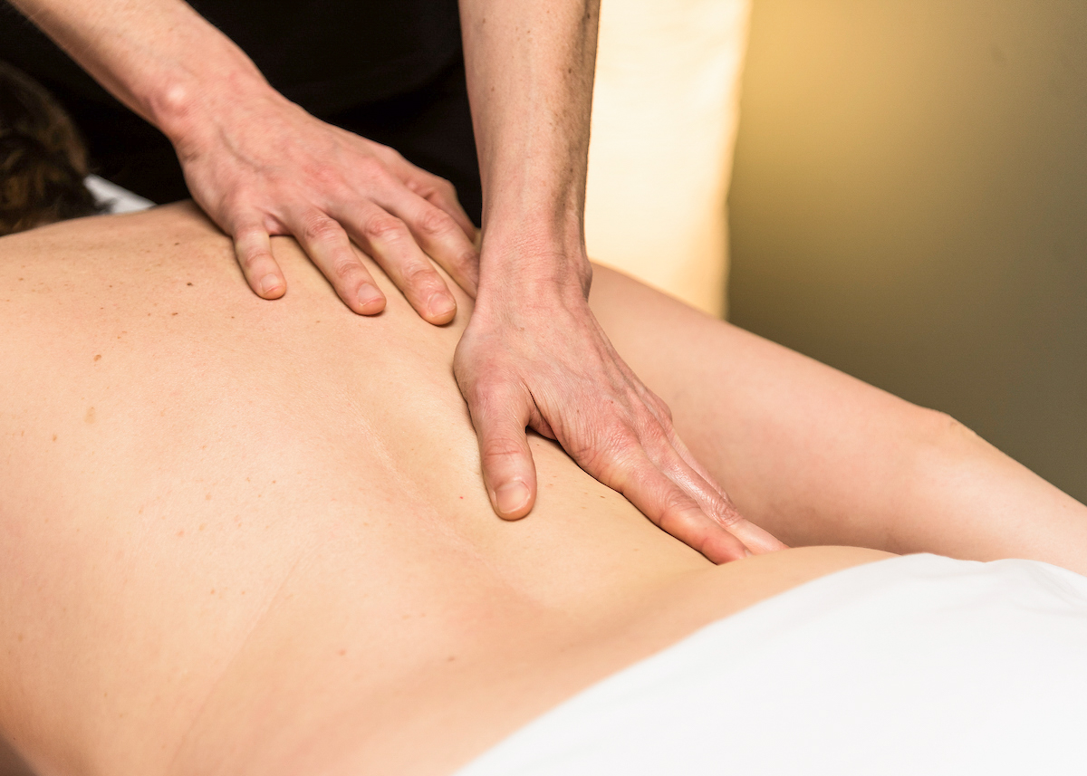 Hands massaging a person's back