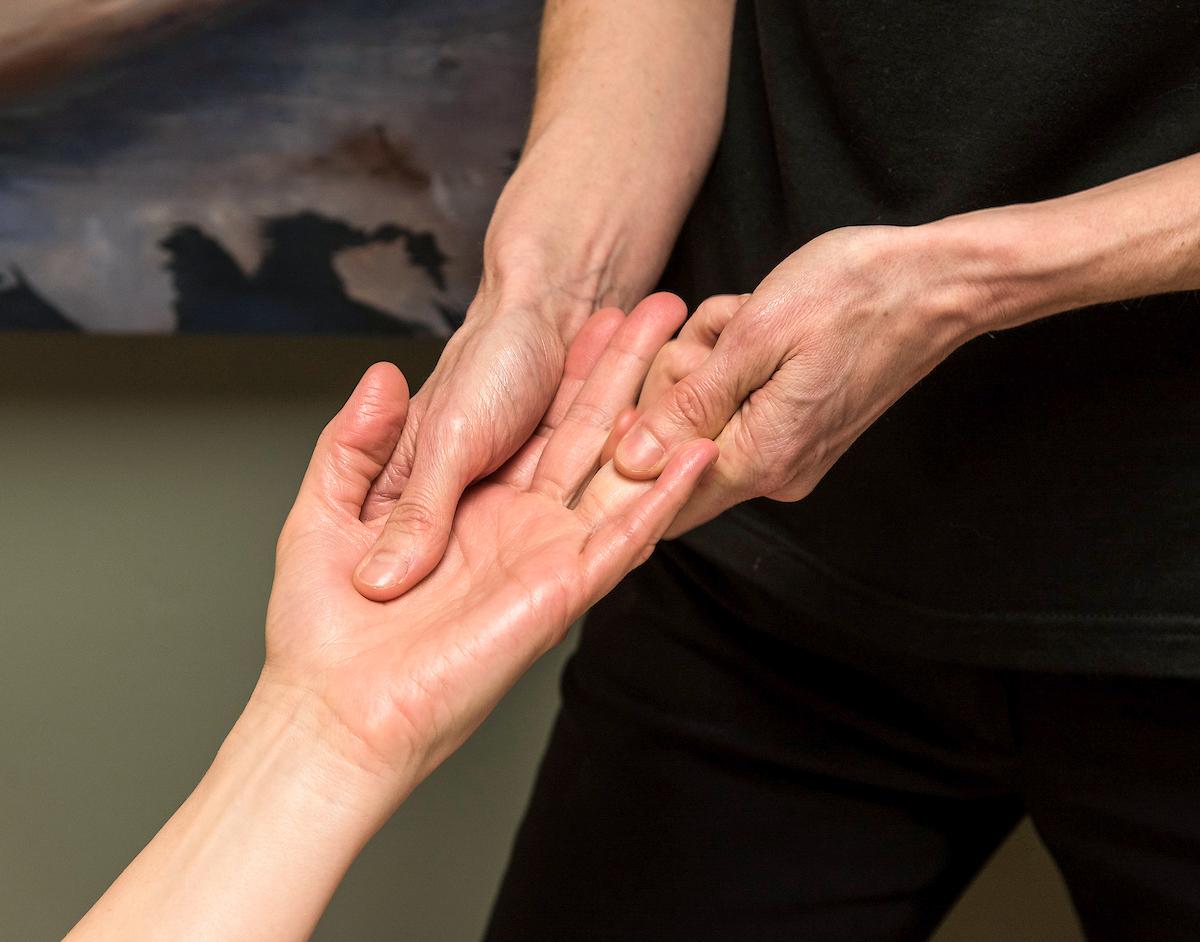 Close-up of hands massaging a hand