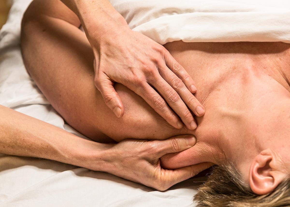 Closeup photo of hand massaging a person's left shoulder