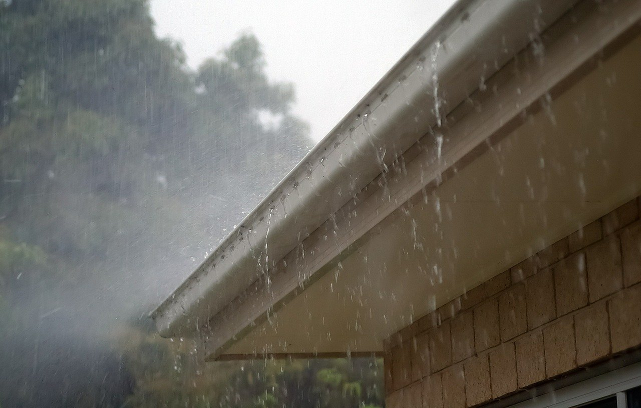 heavy rain overflowing a clogged gutter