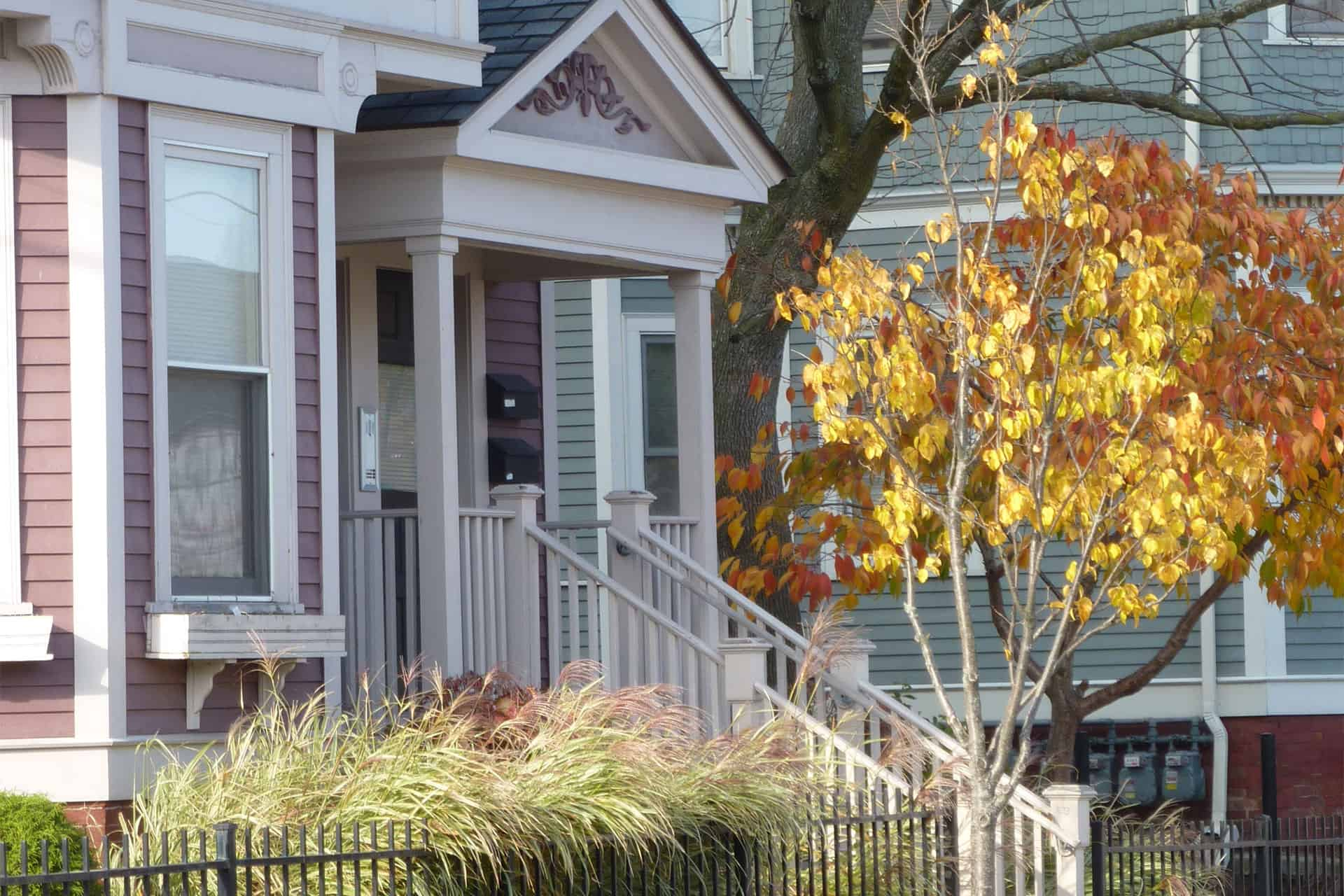 The time of year is the fall. Off to the right is a small tree with yellow leaves. To the left is a restored historic Victorian home showing the front porch and front windows.